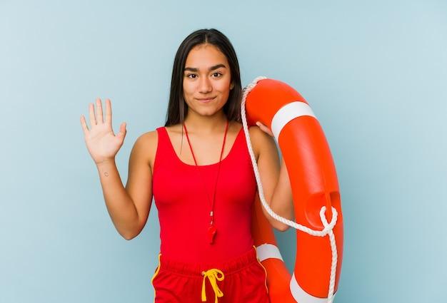 Молодая азиатская женщина спасателя изолировала усмехаясь жизнерадостный показ номер 5 с пальцами.