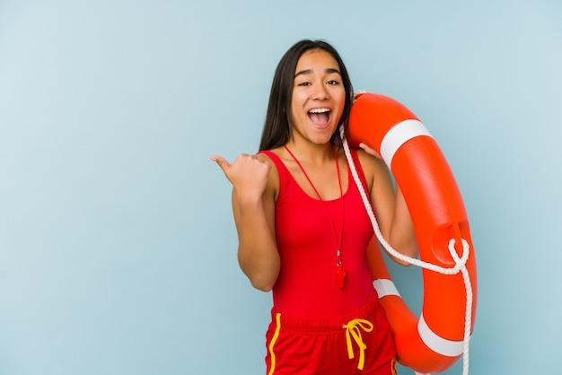 Молодые азиатские спасатель женщина указывает пальцем в сторону, смеется и беззаботный.