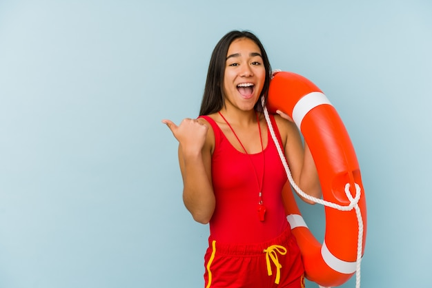 Young asian lifeguard woman points with thumb finger away, laughing and carefree.