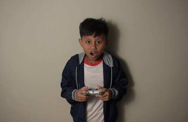 젊은 아시아 소년은 흥분하고 놀란 표정으로 손을 잡고 게임 플레이
