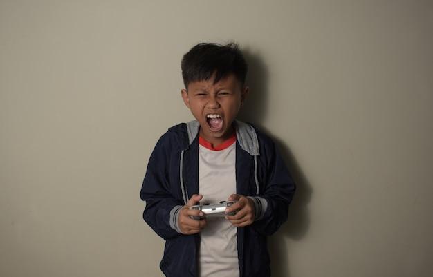 어린 아시아 소년은 흥분한 표정과 소리를 지르며 손을 잡고 게임 플레이를 제어합니다.