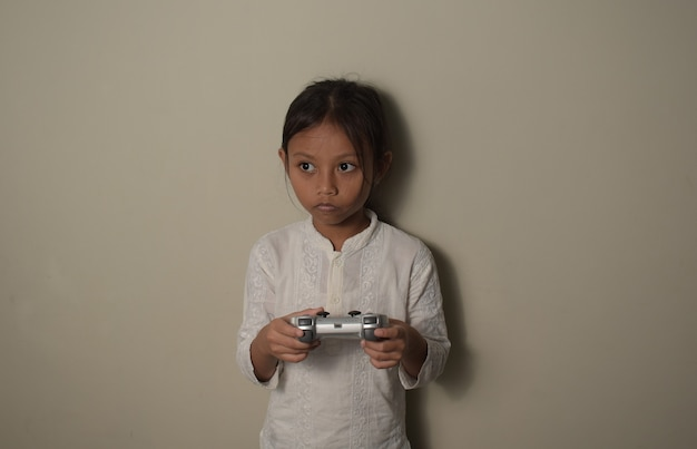 Молодая азиатская маленькая девочка, взявшись за руки, контролирует игровой процесс с сосредоточенным выражением лица