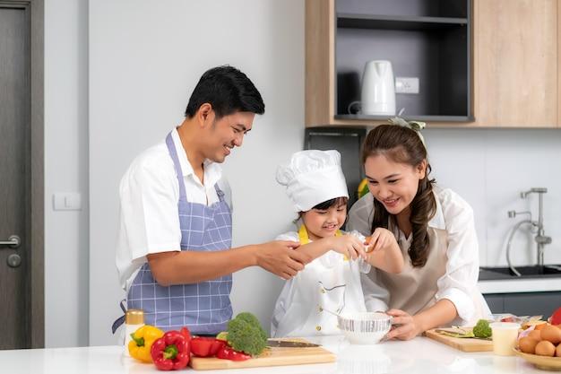 젊은 아시아 사랑 가족은 부엌에서 테이블에 음식 저녁 식사를 준비하고 있습니다