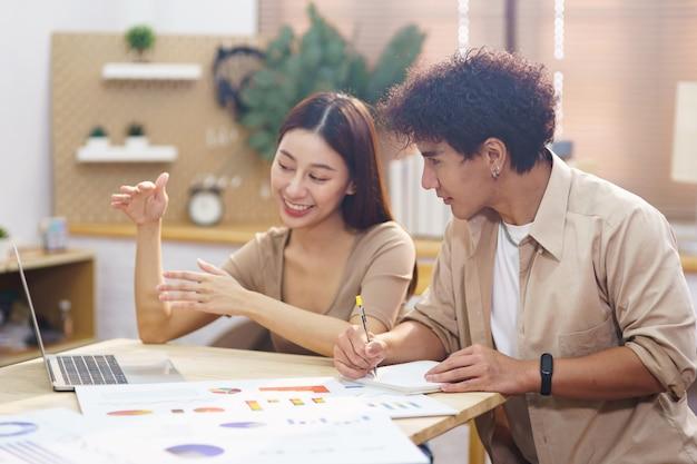 Молодые азиатские мужчины и женщины в качестве фрилансера сидят в гостиной, используя ноутбук и изучают финансовую диаграмму графика для инвестиций. пара учится и работает в интернете, чтобы начать малый бизнес в домашнем офисе