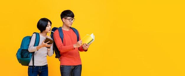 다채로운 캐주얼 옷을 입고 젊은 아시아 남성과 여성의 학생들은 책을보고