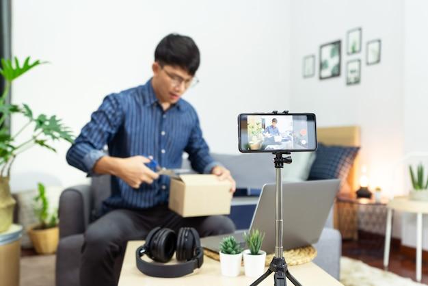 젊은 아시아 남성 블로거가 홈 오피스에서 제품의 카메라 리뷰에 동영상 블로그 동영상을 녹화하고, 삼각대 장착 카메라 화면에 초점을 맞춰 소셜 네트워크에 라이브 스트림 동영상을 방송했습니다.