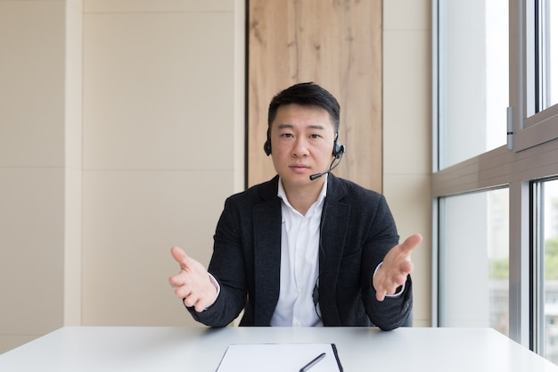 カメラを見てビデオ通話、会議、会議でオンラインで話している若いアジア人男性実業家。ウェブカメラビュー。屋内でビジネススーツを着たアジア人。オフィス交渉距離相談やアドバイス