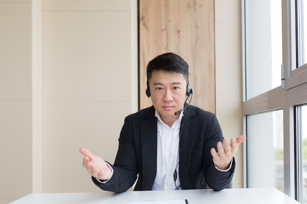Young asian male businessman talking online on video call, conference or meeting looking at camera. webcam view. asia man in business suit indoors. office negotiations distance consultation or advice
