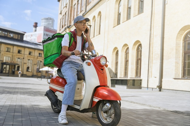 보온 가방을 들고 c와 전화 통화를 하는 젊은 아시아 남성 택배