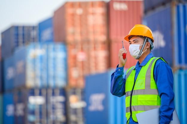 젊은 아시아 남성 엔지니어 또는 관리자 산업 운송 및 물류 개념에서 컨테이너 부하를 제어하기 위해 무선 통신 및 랩톱 컴퓨터를 사용합니다.