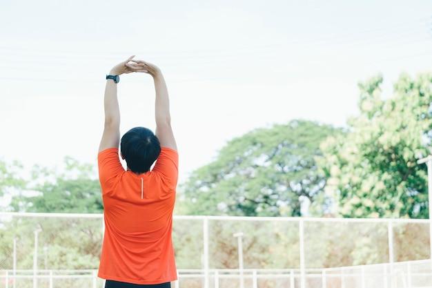 走る前に腕と上半身を伸ばしてウォーミングアップする若いアジア人男性ジョガー。