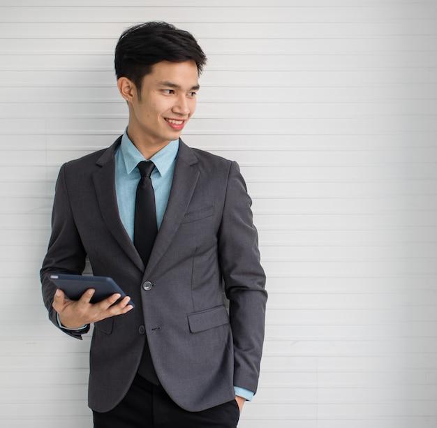 壁の近くに立っている間笑顔と目をそらしている現代のタブレットを持つ若いアジア人男性マネージャー