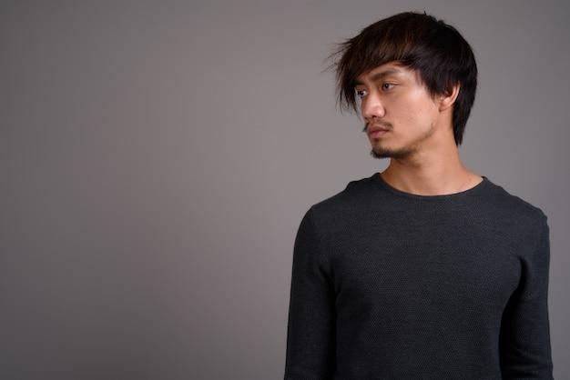 Молодой азиатский человек против серой стены