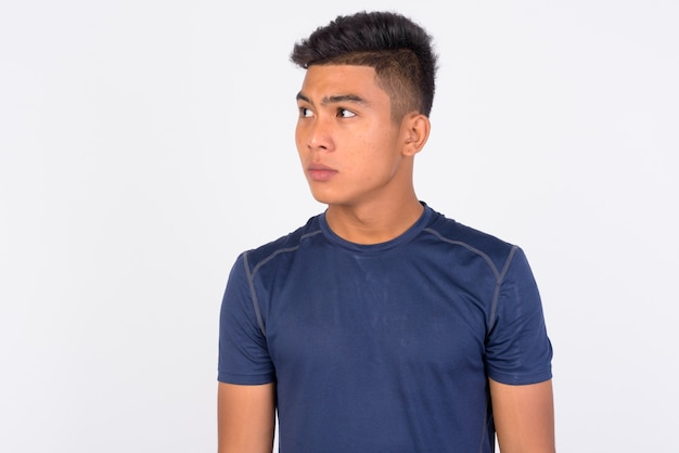 Young asian man against white wall