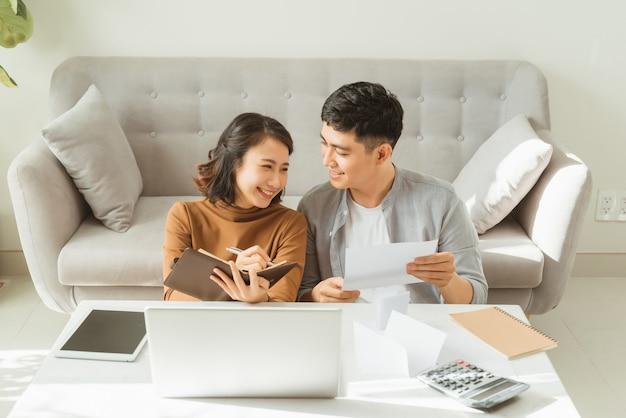 若いアジア人の男性と女性は、オフィスでの彼女のビジネスオンラインショッピングでストレスを感じています。