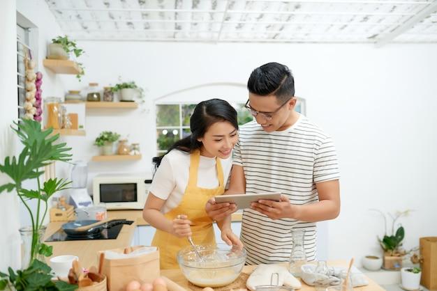젊은 아시아 남성과 여성이 함께 케이크와 빵을 계란과 함께 요리하고 밀가루에 담긴 태블릿으로 메뉴를 보고 집에서 행복하게 쉬고 있다