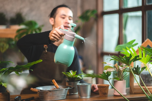 Young asian man are happy with growing plant in small green garden at home, hobby lifestyle with green nature in a house, flower tree in pot to botanical gardening agriculture cultivation