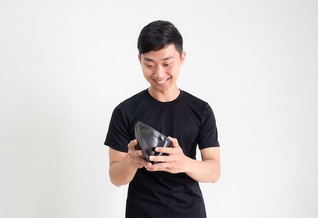 젊은 아시아 남자 검은 셔츠는 웃는 얼굴로 지갑에 있는 현금을 보고 행복합니다