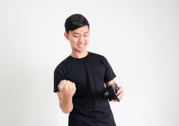 젊은 아시아 남자 검은 셔츠는 손에 지갑에 돈과 함께 주먹과 행복한 얼굴을 보여줍니다