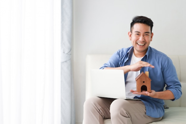 Young asian man in blue shirt with laptop computer and little house model showing for bank loan for house concept in living room