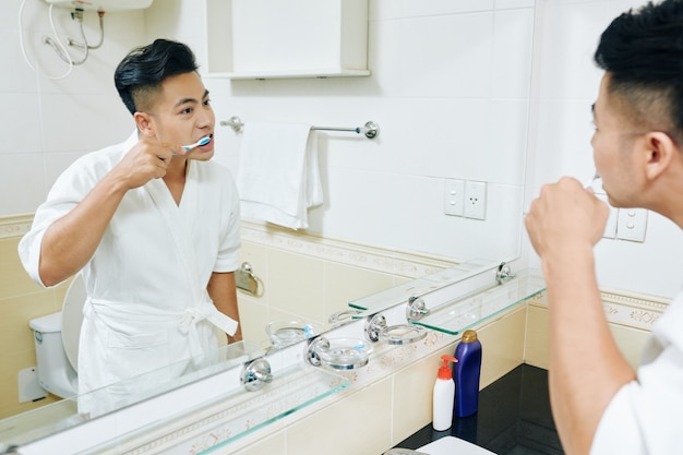 Young asian man brushing teeth