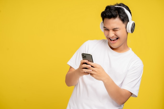 Young asian man in casual clothes are happy to listen to wireless headphones. he is listening to song on his smartphone on yellow background.