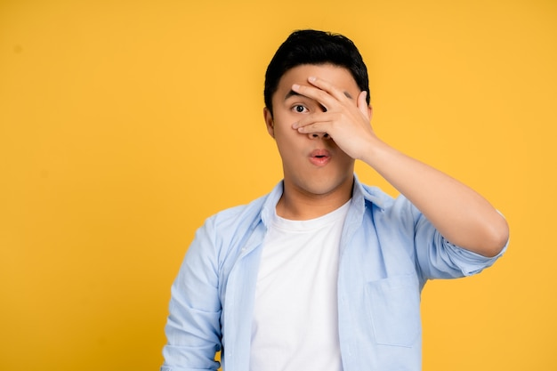 Young asian man in casual clothes is shocked. he was covering his face and eyes with his hand, looking through his fingers with a frightened expression on a yellow background.