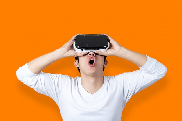 Young asian man in casual white outfit holding or wearing vr glasses by hands looking up