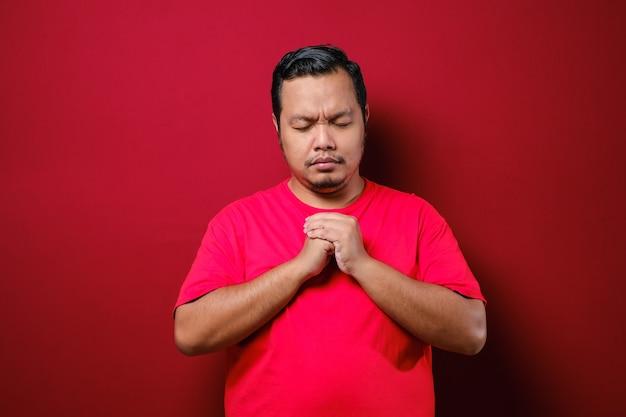 젊은 아시아 남자는 눈을 아래로 향하게 하고 손을 잡고, 소원을 표현하고, 빨간색 배경 위에 기도하고 희망 제스처를 합니다.