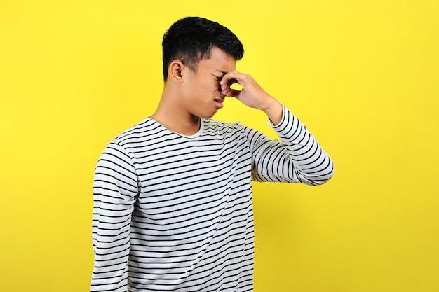 젊은 아시아 남자는 노란색 배경에 고립 된 나쁜 냄새에 대해 코를 닫습니다