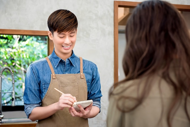 Young asian man coffee shop staff taking order from the customer