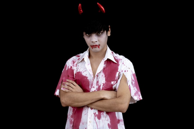 Young asian man costume in hell, evil on black wall with concept for halloween fashion festival. teen asian man in cosplay halloween.