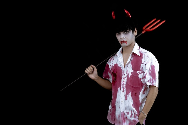 Young asian man costume in hell, evil on black wall with concept for halloween fashion festival . teen asian man in cosplay halloween.