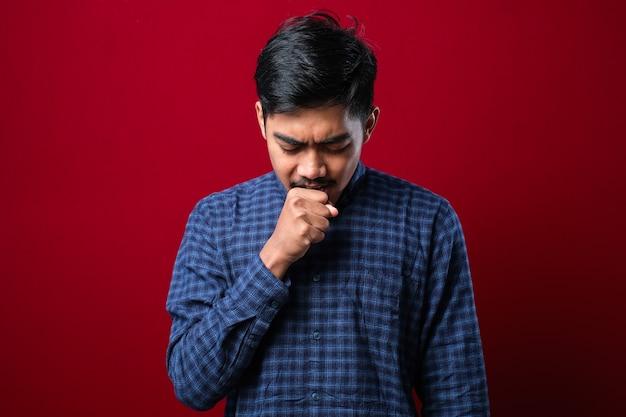 喉の痛みで咳をする若いアジア人男性、赤い背景にアレルギーを持つ男の概念
