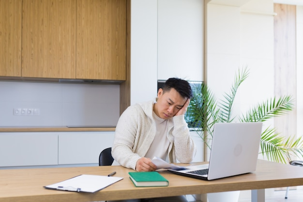 Young asian man counts bills bank checks loans or utilities while sitting at home