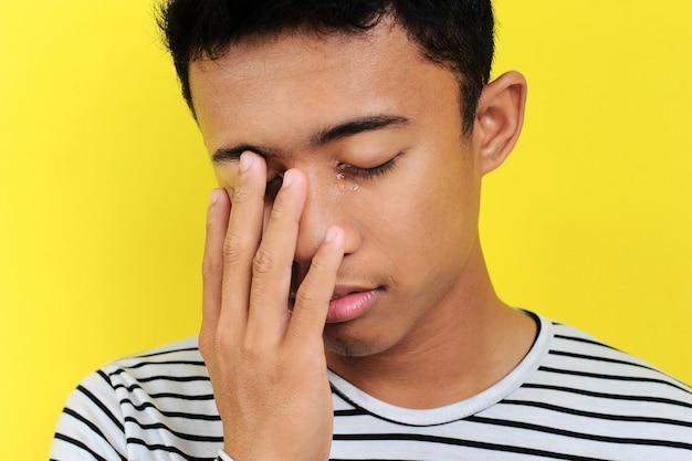 若いアジア人の男が泣く、黄色の背景に分離
