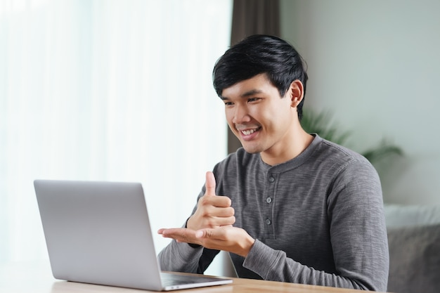 Young asian man deaf disabled using laptop computer for online video conference call learning and communicating in sign language.