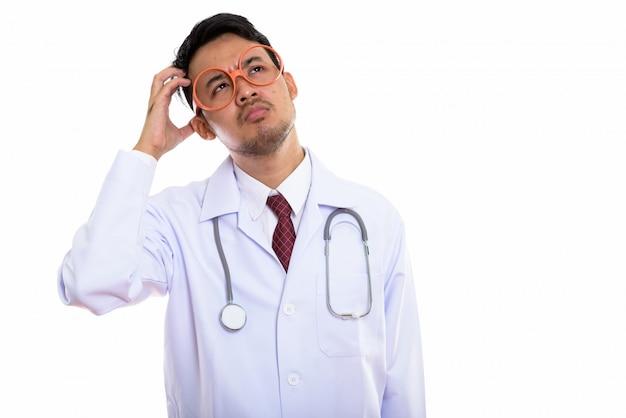 Молодой азиатский мужчина доктор думает во время царапин