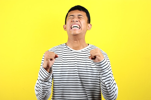 Young asian man doing angry gesture, annoyed, and emotional, isolated on yellow background