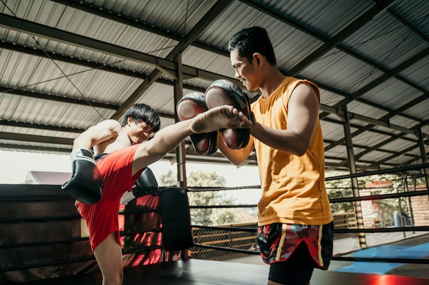 Young asian man doing kickboxing training with her coach. man on boxing training