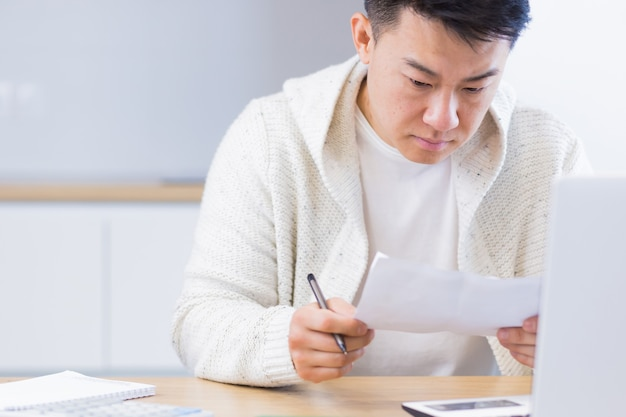 책상에 앉아 집에서 서류 작업을 하는 젊은 아시아 남자