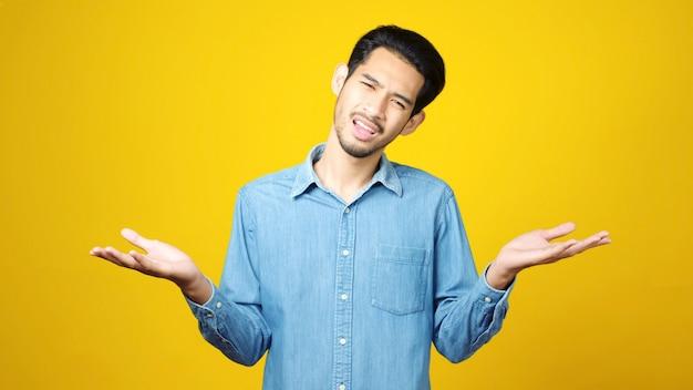 Молодой азиатский человек сомневаясь стоя. выражение отрицательного вкуса людей
