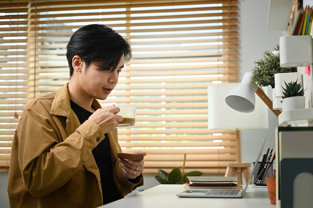 Молодой азиатский мужчина пьет кофе и читает электронную почту на портативном компьютере.