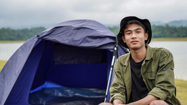 若いアジア人男性は貯水池でキャンプを楽しんでいます