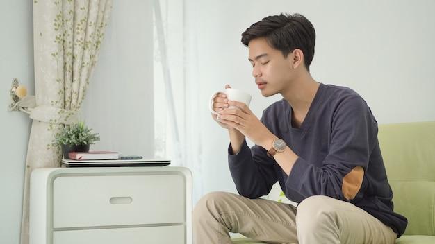 Молодой азиатский мужчина, наслаждаясь напитком дома после работы