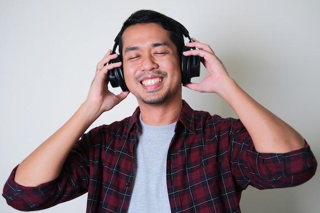 Young asian man enjoying music using headset