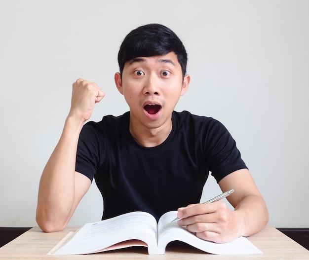 젊은 아시아 남자는 충격을 받은 흥분된 얼굴을 느끼고 책상 위에 있는 책을 들고 카메라를 쳐다본다