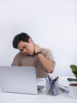若いアジア人男性はオフィスで気分が悪く、オフィス症候群による仕事関連の痛みに苦しんでいます。白い背景で隔離のスタジオショット。