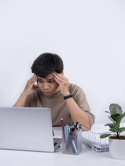 젊은 아시아 남자는 사무실에서 기분이 나쁘고 일하면서 스트레스가 많은 두통이 있습니다. 스튜디오 촬영에 고립 된 흰색 배경.
