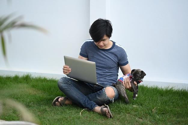 裏庭で草の上に座っている間彼の犬と若いアジア人男性フリーランサー